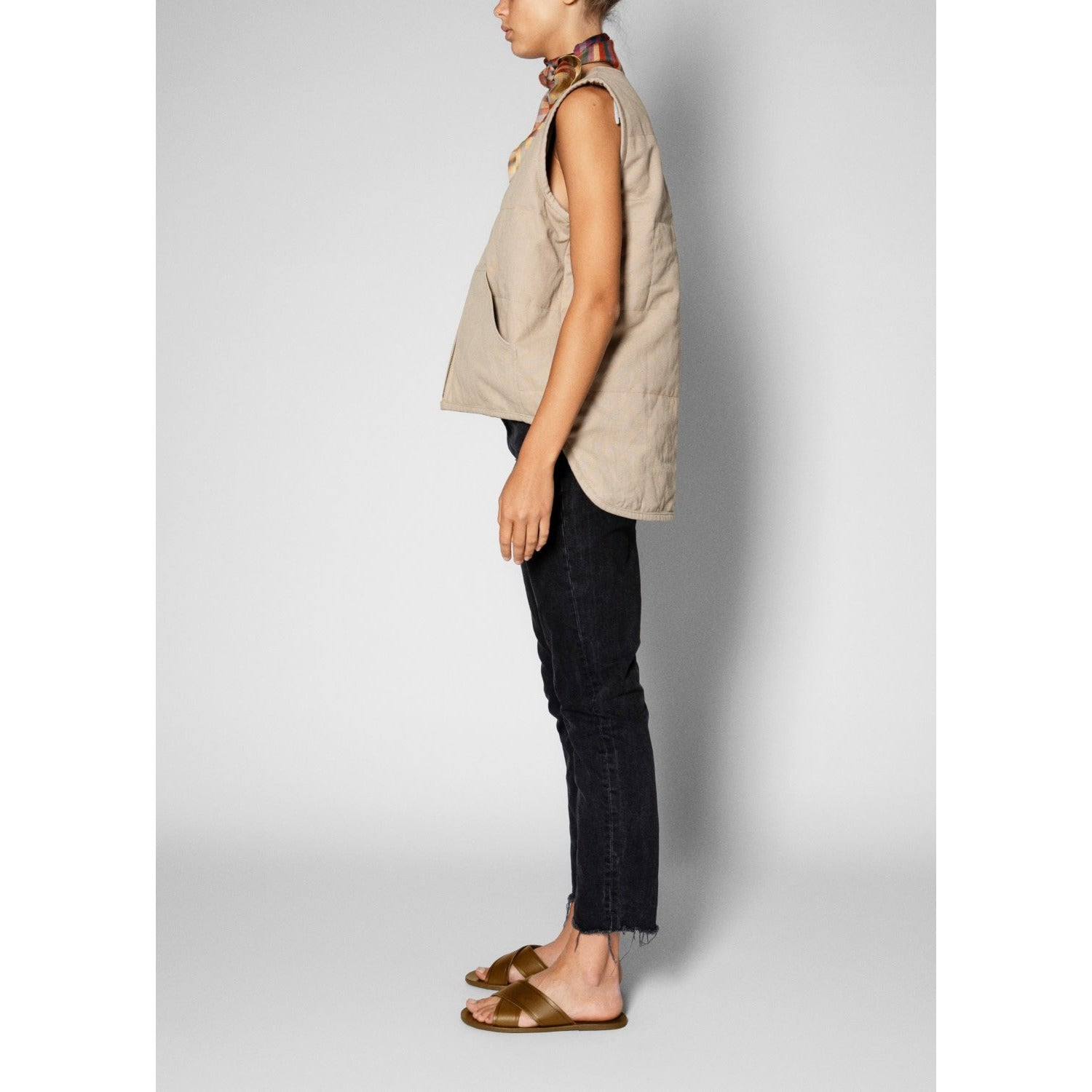 beige zip up vest worn with black pants and sandals