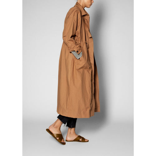 model wearing ankle length brown organic cotton coat with her hands in the pockets