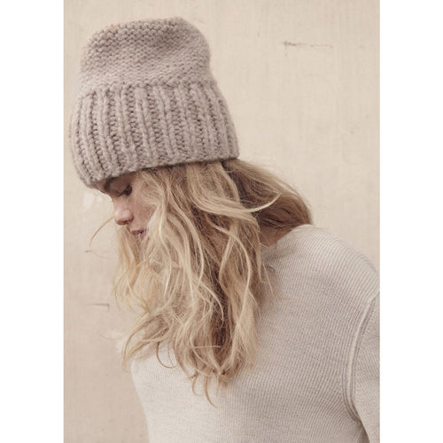 model wearing a light brown cashmere knit beanie