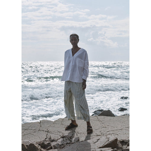 white button up shirt paired with flowy striped pants, worn by a model at the beach
