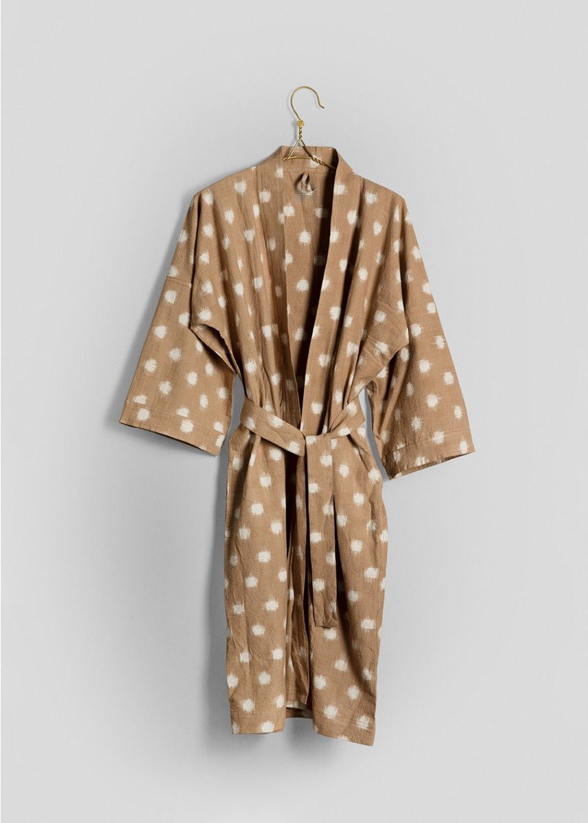 beige and white dotted bathrobe hung on a hanger