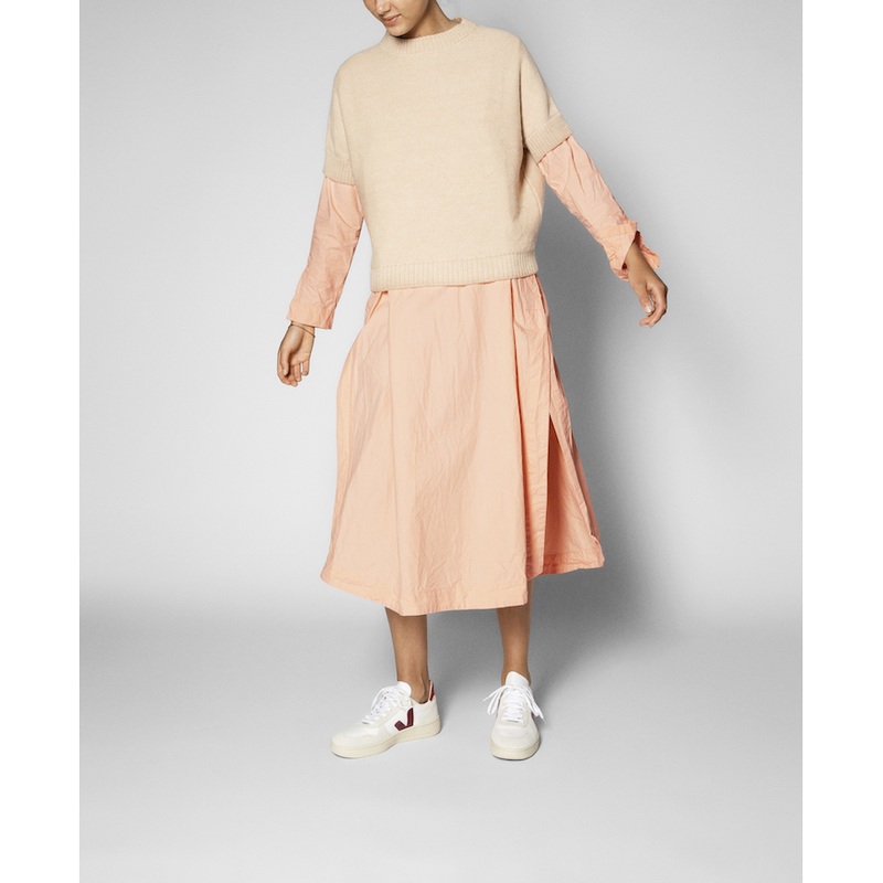 cream colored short sleeve sweater worn over a long sleeve pink dress