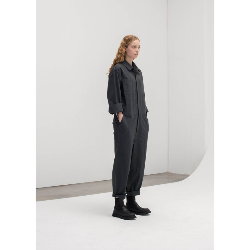 model wearing dark grey jumpsuit with black boots