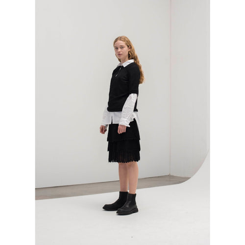 three tiered black lace skirt worn with a white button up and a black quarter sleeved blouse
