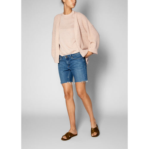 light pink loosely-knitted cardigan draped over a pink tee-shirt, paired with a pair of jean shorts and sandals
