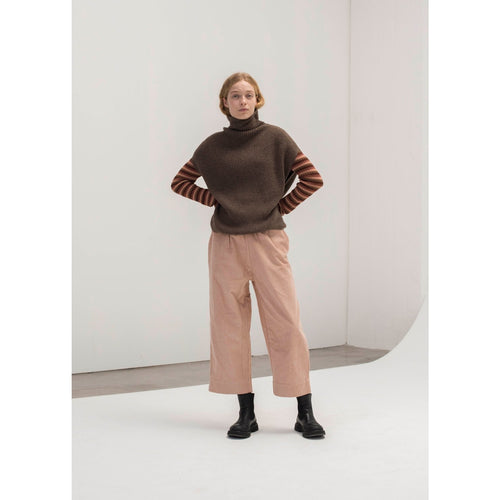 brown knit loose sweater vest with a turtleneck, worn over a striped long sleeve, with pink pants