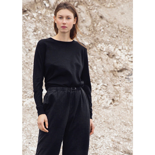 model wearing black cashmere sweater tucked into black pants