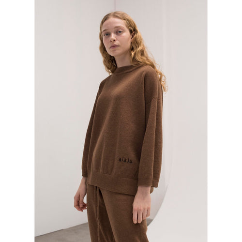 "model wearing a tobacco colored sweater with ""aiayu"" stitched into the lower corner, and a matching pair of sweats"
