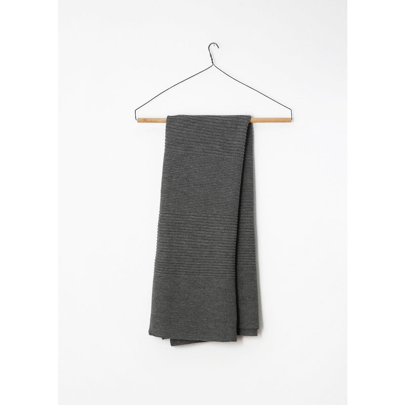 folded dark grey cashmere blanket hung from a hanger on a wall