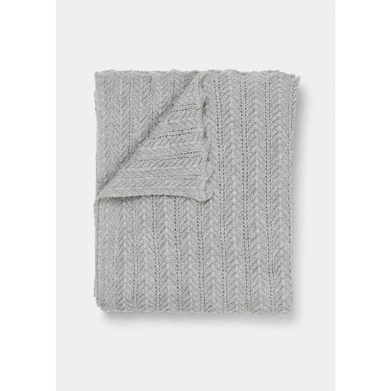 folded light grey knit throw with scalloped edge