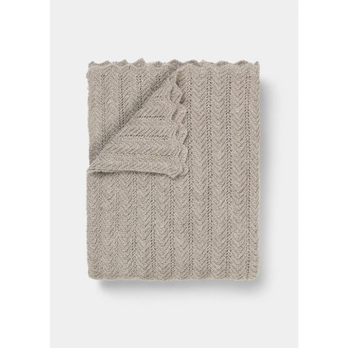 light tan knit throw folded with scallop edge