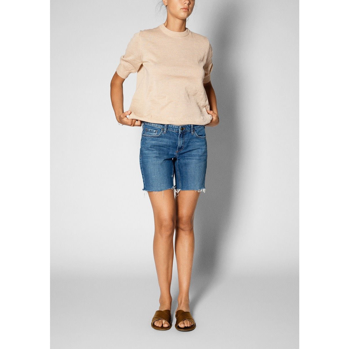 model wearing light pink short sleeve sweater with a pair of denim shorts