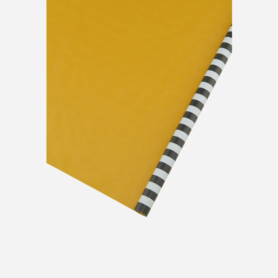 black and grey striped wrapping paper with a yellow underside