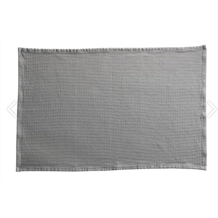 rectangular bath mat in a light grey color by designer tine k