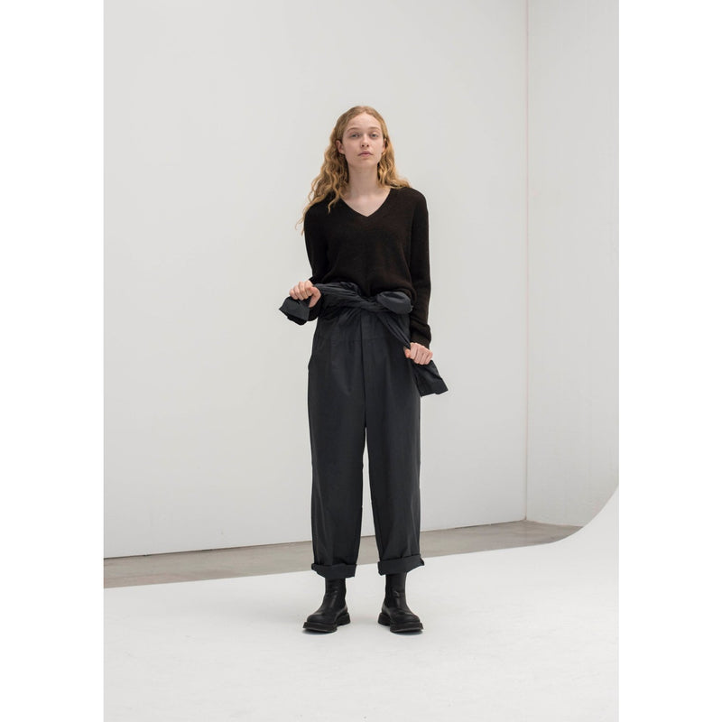 black vneck long sleeve sweater tucked into a tied off grey jumpsuit