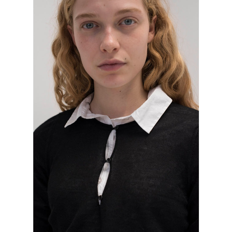 model wearing knit sweater with button details over a white button up, with the collar poking out