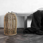 domed rattan lantern next to a bench with a blanket draped over it