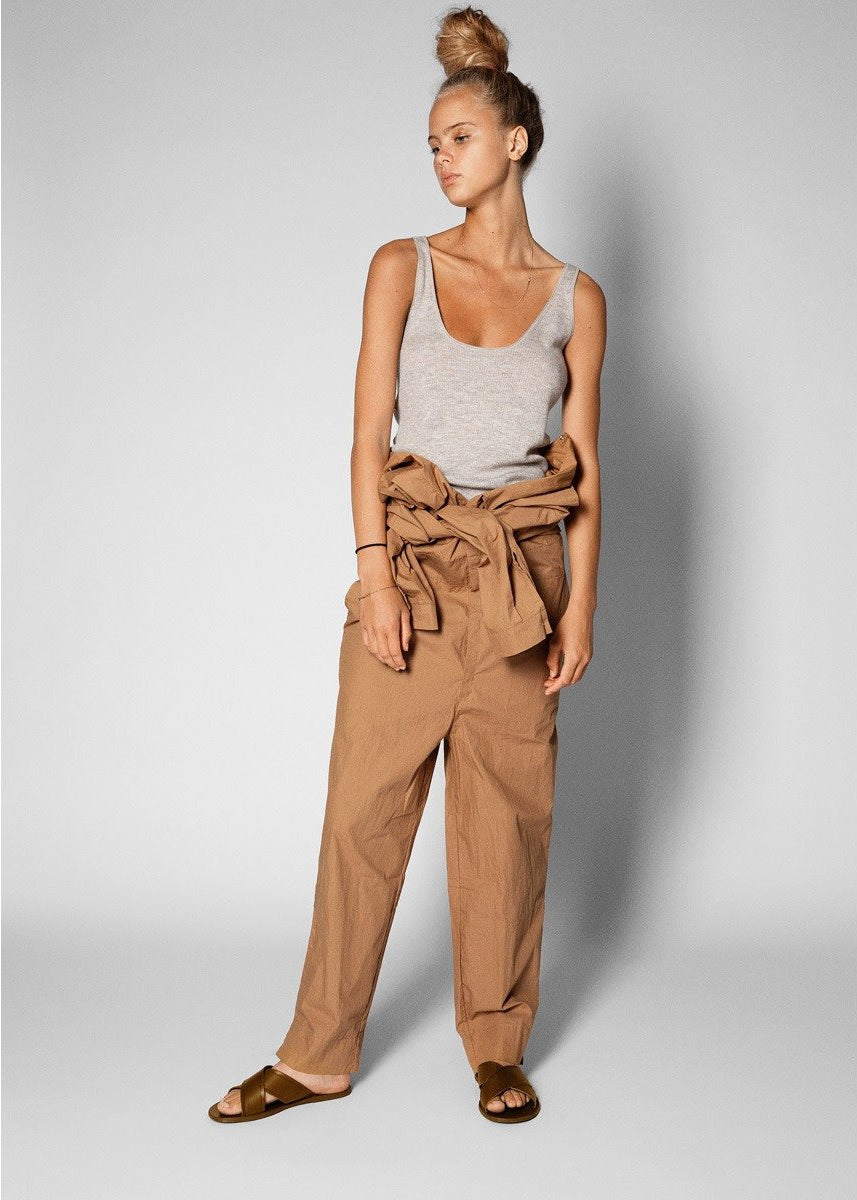 model wearing grey cashmere tank top with undone tan jumpsuit tied at the waist