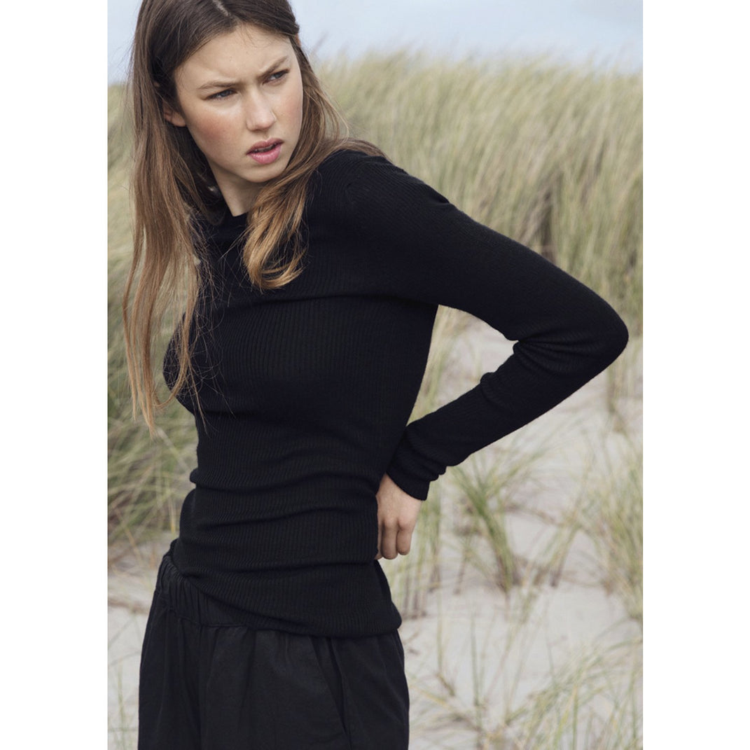 model wearing ribbed black cashmere pullover with black pants