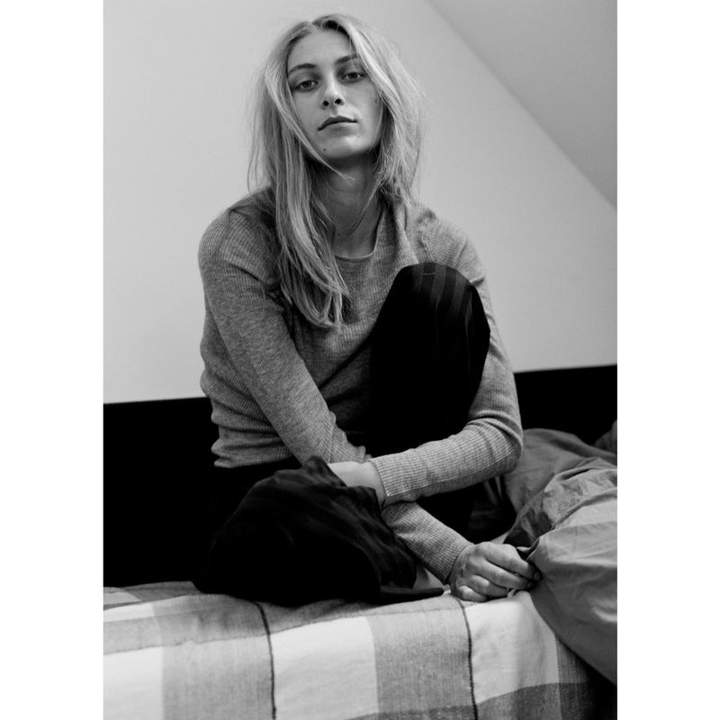 black and white photo of model lounging on a bed in cashmere pullover and sweats