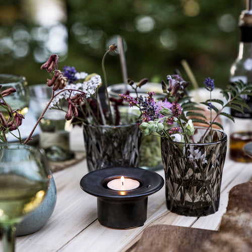 black earthenware glazed candle holder with tea light inside, on a table with glasses filled with flowers