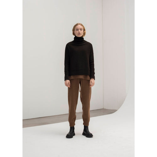 model wearing a chocolate turtleneck sweater with brown pants and boots