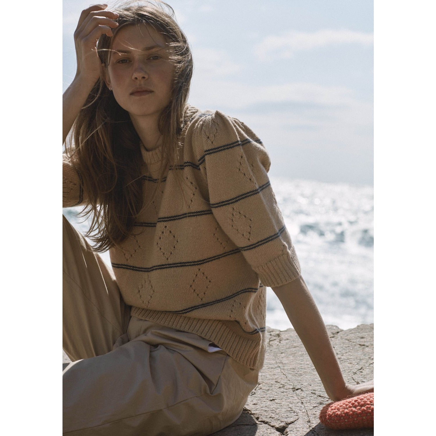 close up of model sitting down wearing sand and navy striped quarter sleeve sweater with puffy sleeve detail
