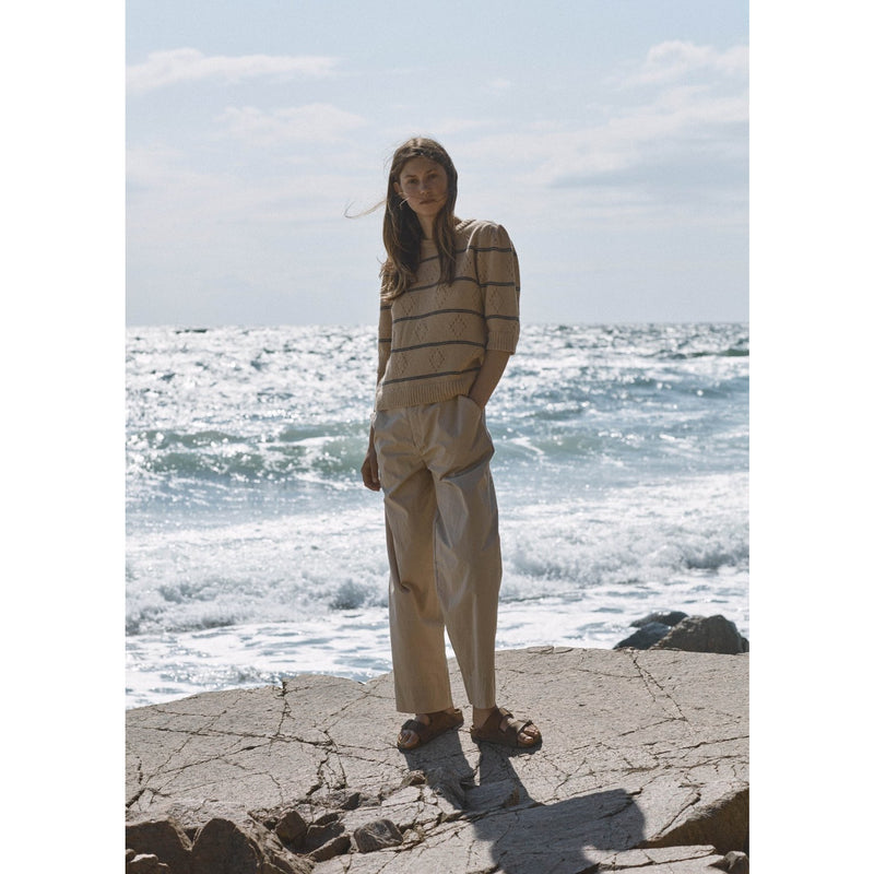 model wearing sand and navy striped quarter sleeve sweater with a pair of cotton pants in a similar tone