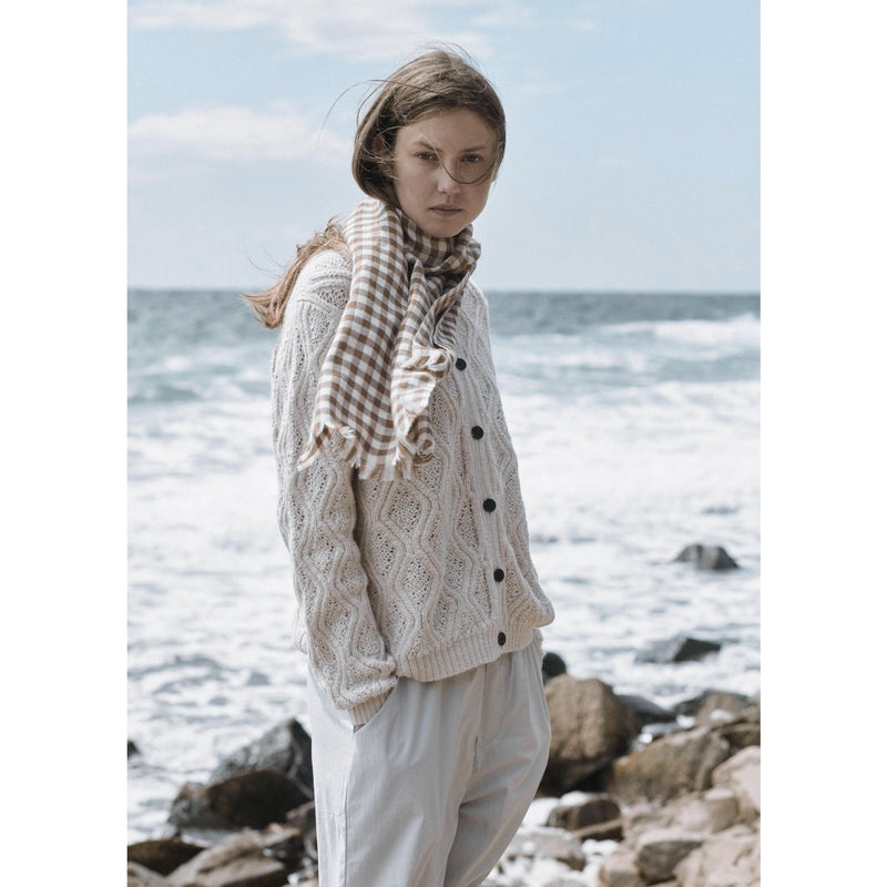 model wearing white knit cardigan with similar toned scarf and pants