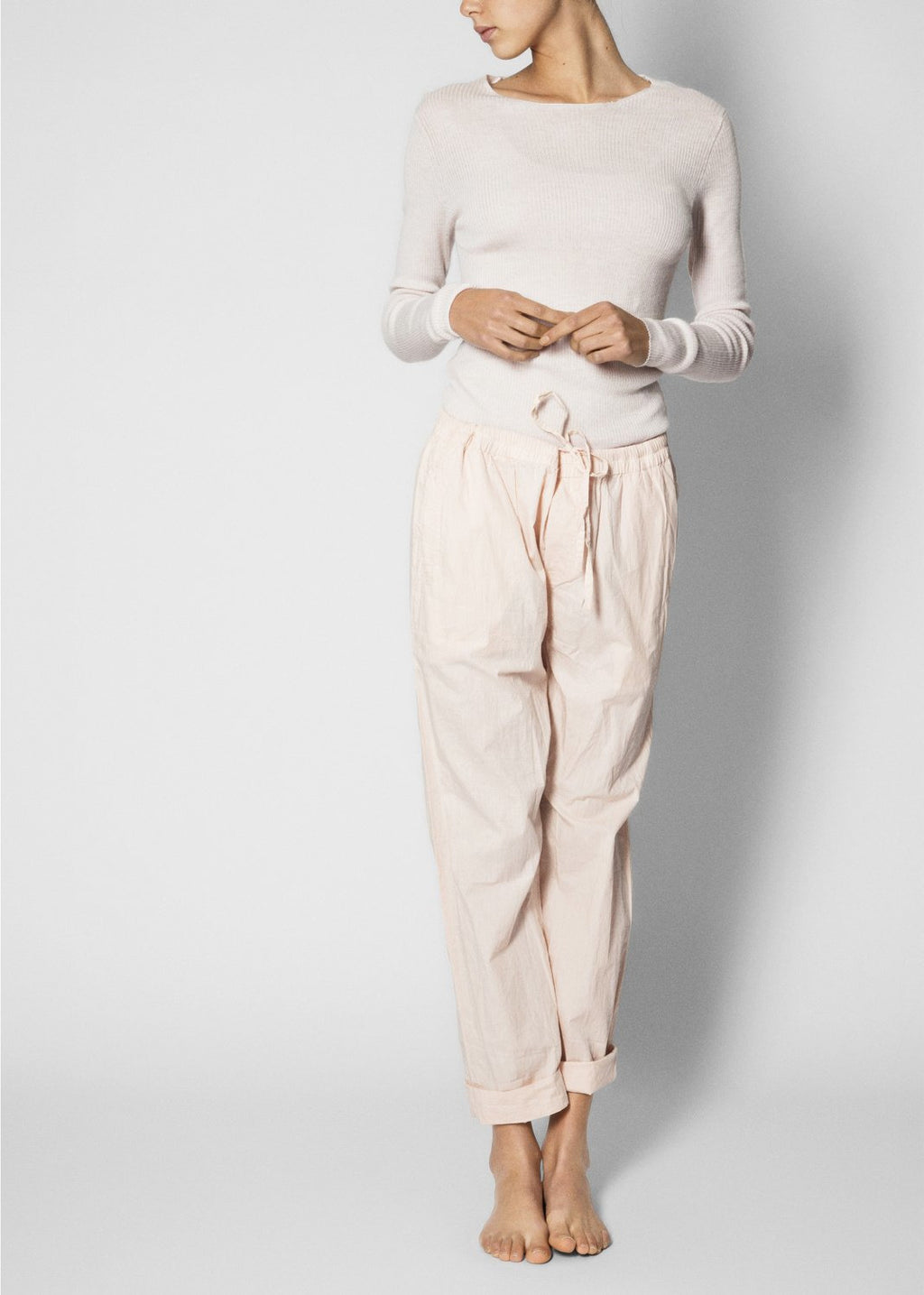 model wearing light pink organic cotton pants and a white top