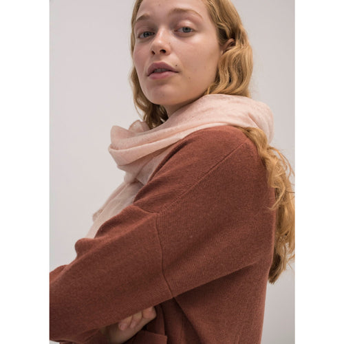 model wearing light pink cashmere scarf with a rust colored sweater