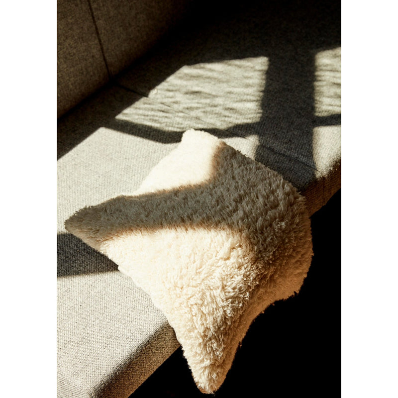 white puffy pillow draped on a bench, shadowed