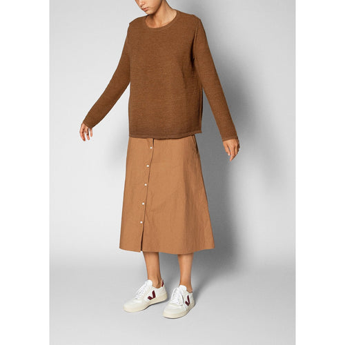 brown long sleeve sweater worn over a tan a-line skirt with white sneakers
