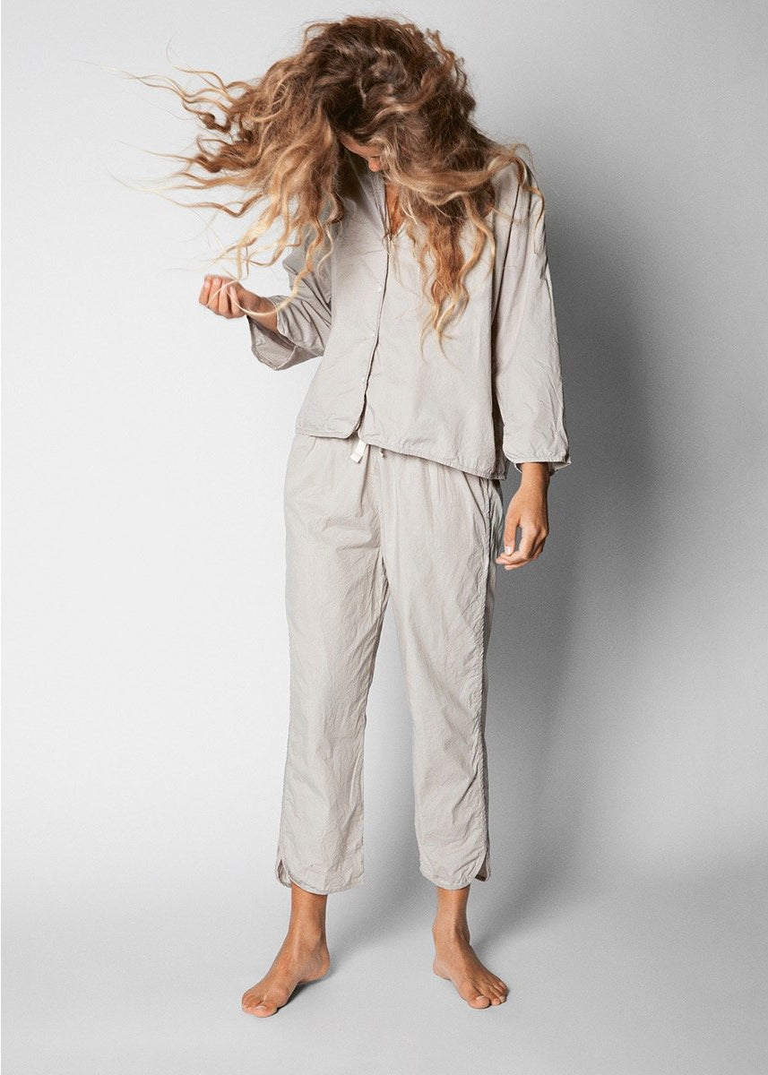 model wearing grey set of organic cotton pajamas and swinging her hair