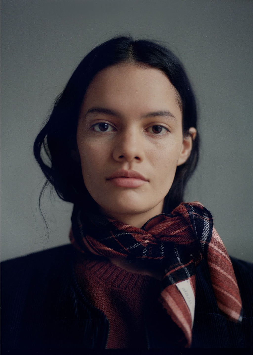model wearing rust, orange, and black plaid scarf