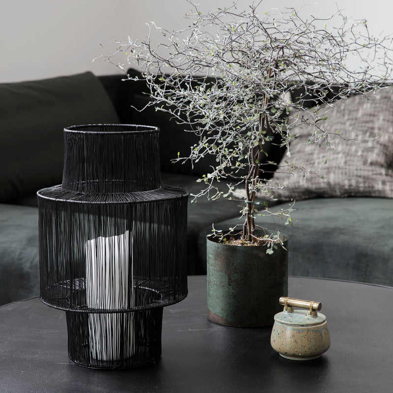 short dark steel lantern next to potted plant and dish resting on a table