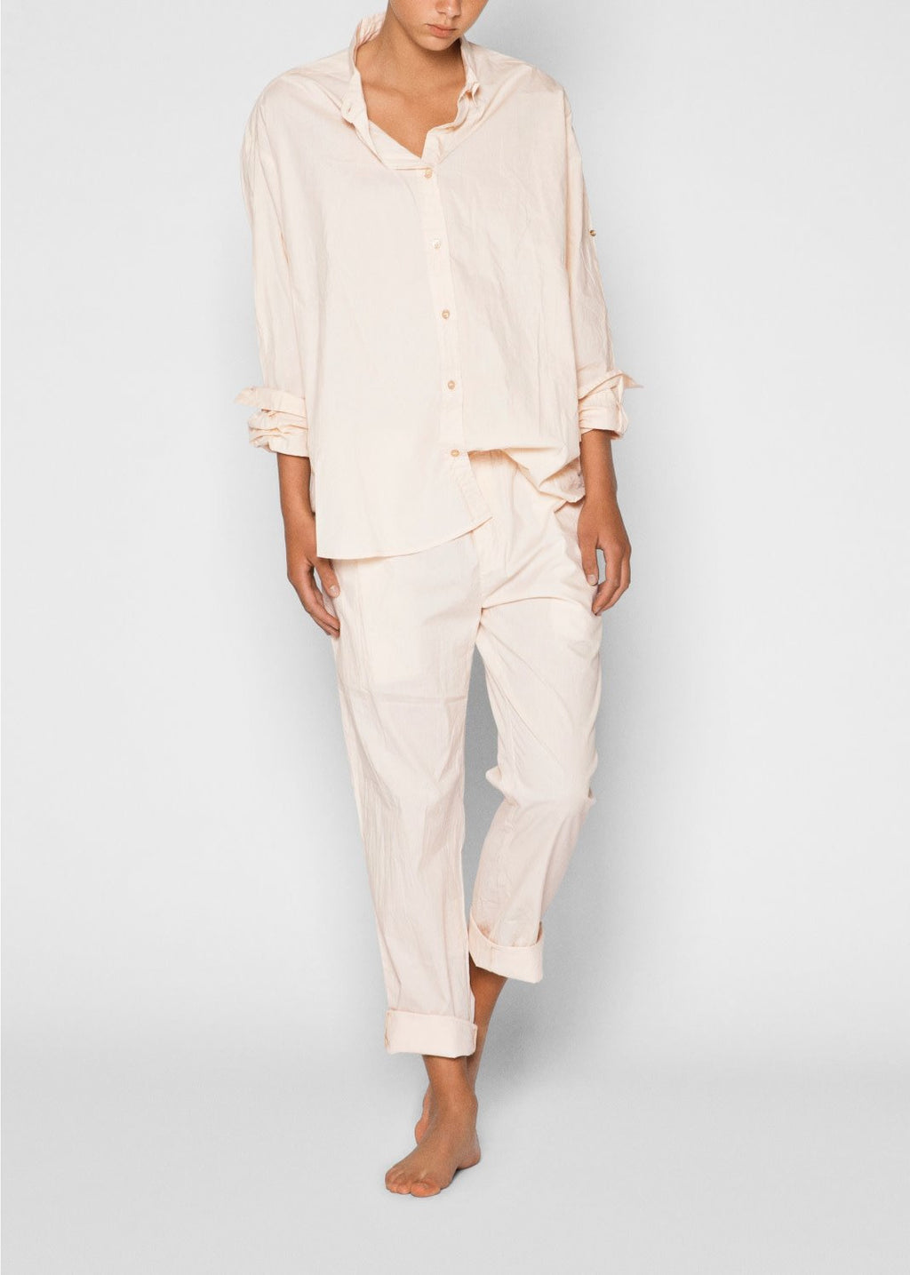 model in blush colored button down and pants