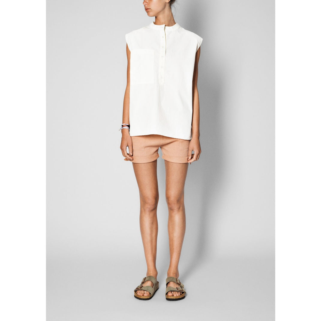 white organic cotton sleeveless blouse paired with pink shorts and sandals