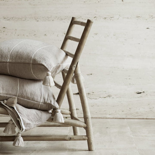 folded bamboo chair with tasseled pillows and a blanket resting on it