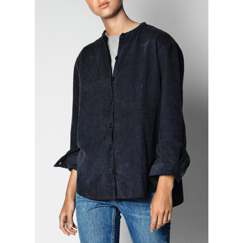 model wearing navy corduroy shirt with the sleeves rolled with a pair of blue jeans
