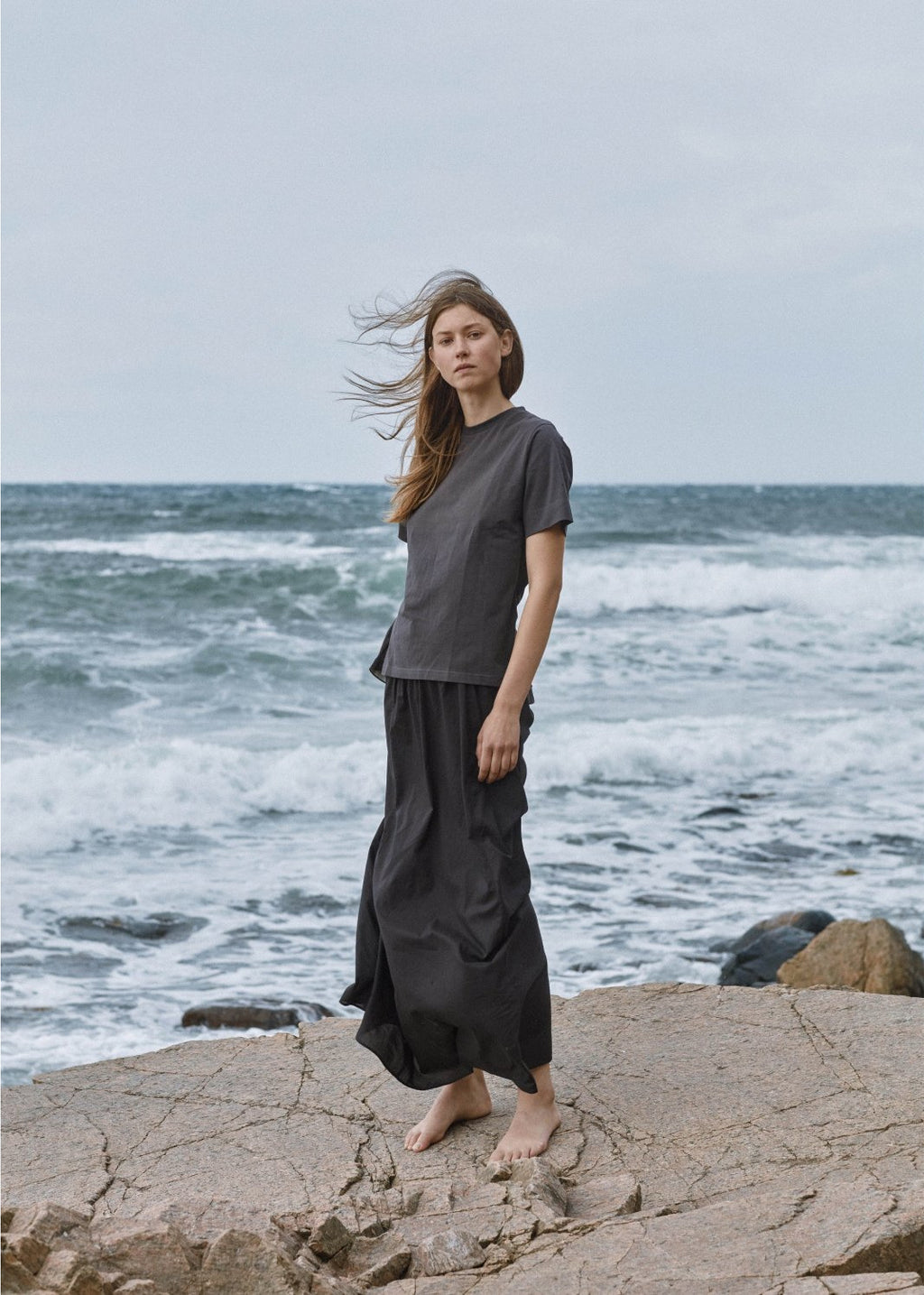 woman at the beach wearing grey boxy tee over flow back pants