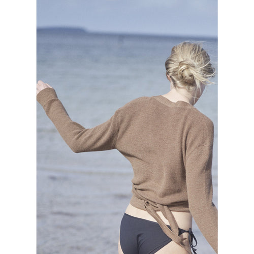 model wearing brown sweater tied at the back with a bathing suit at the beach