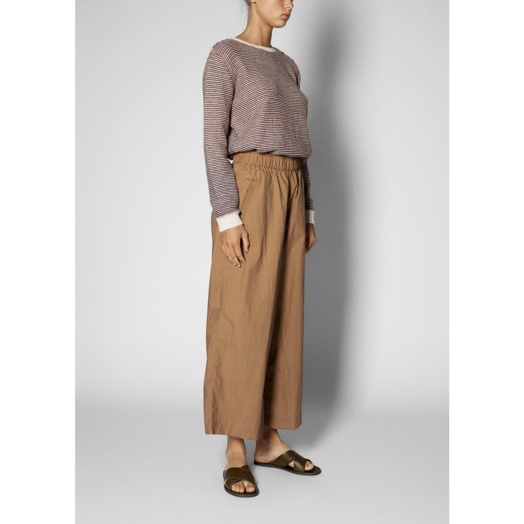 model wearing wide organic cotton pants in light brown with a striped sweater and sandals