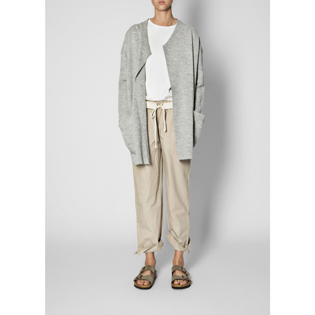 model wearing beige pants with a white tee and grey cardigan and sandals