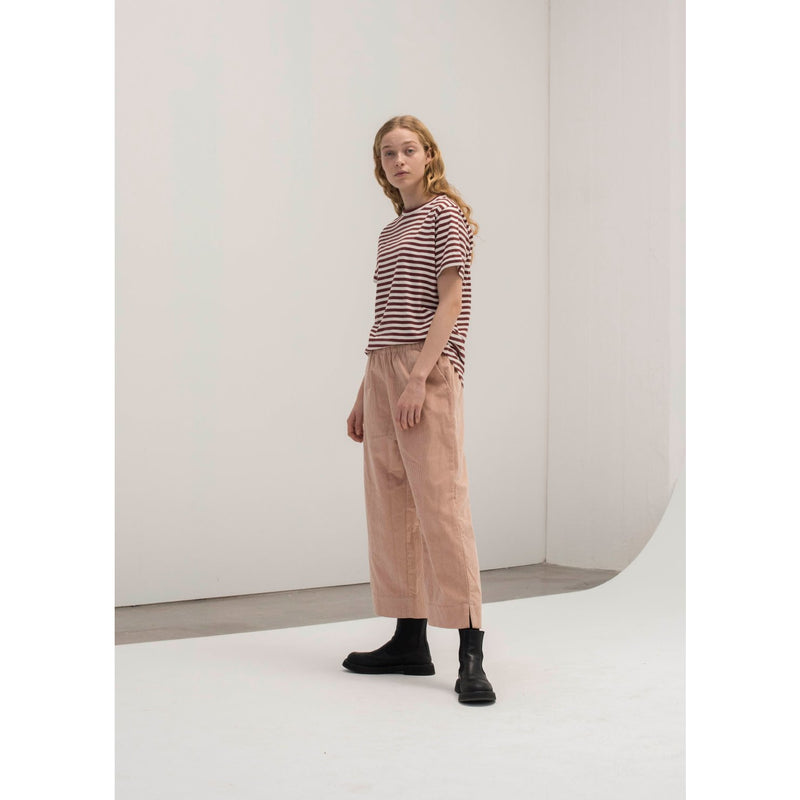model wearing pink corduroy pants with burgundy and white striped shorts sleeve tee and boots