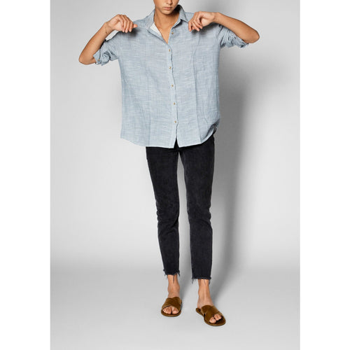 blue and white striped button up with sleeves rolled up, worn with a pair of black pants