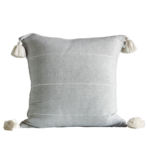square pillow in grey color with cream colored tassels at corners by designer tine k