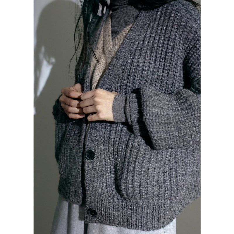 model buttoning her grey knit cardigan over another sweater