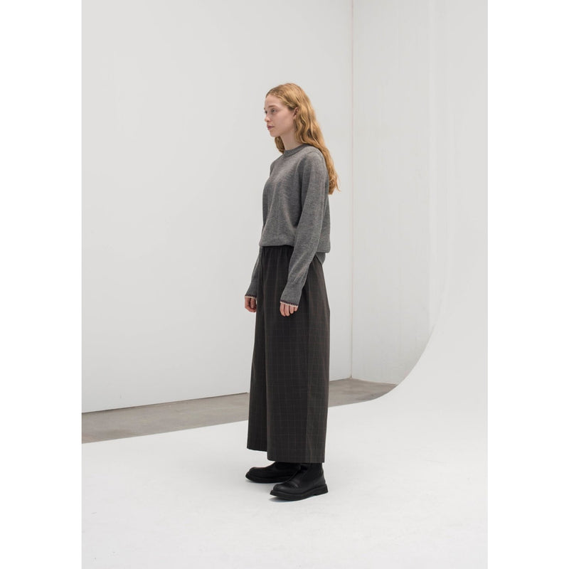 wide legged organic cotton pants in a dark grey, with slight plaid accents worn with a grey long sleeve sweater