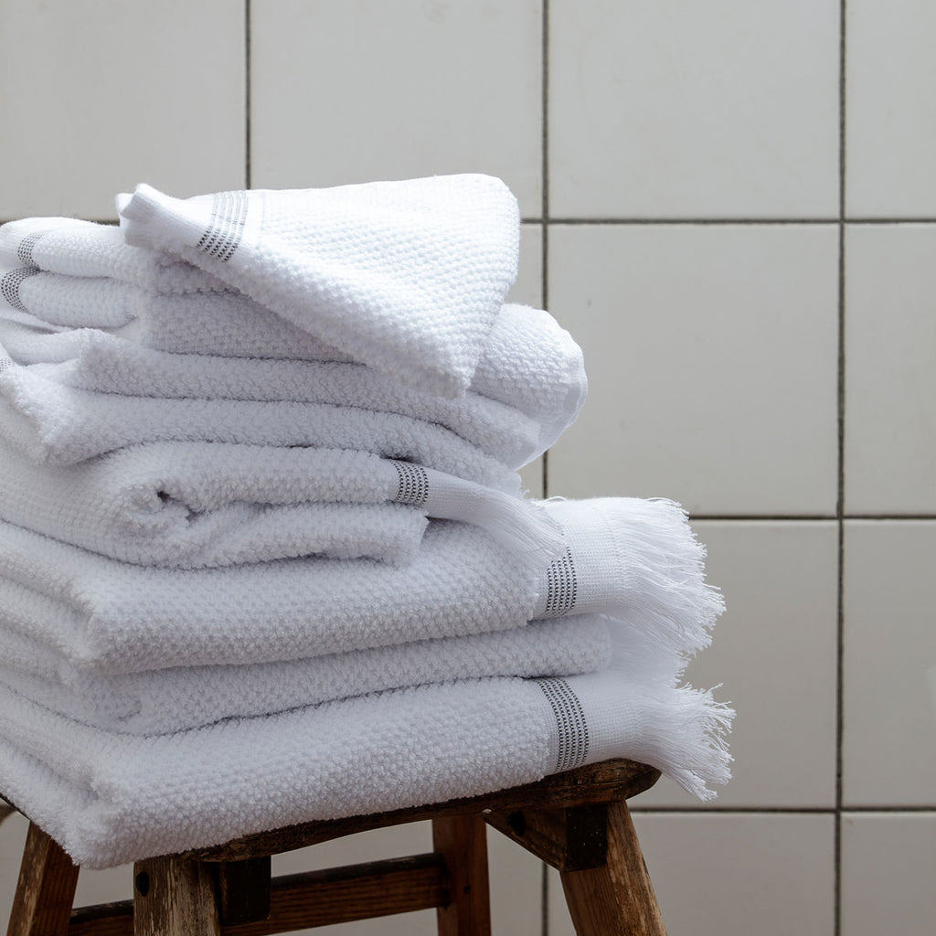 stack of white towels with a grey strip on a stool